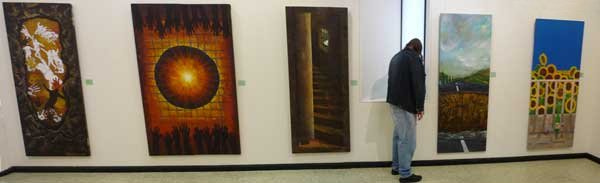 Dac at the exhibition, with five paintings