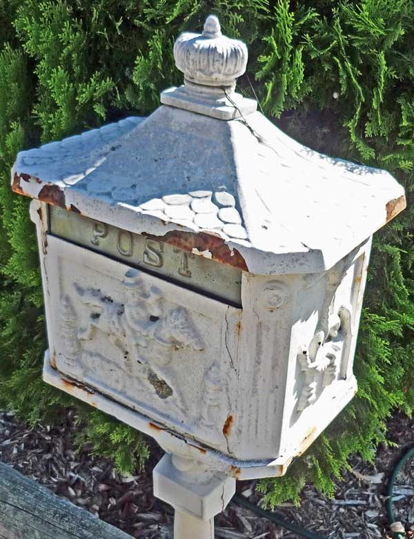 White cast-iron letterbox featuring a crown, a horserider, and post horns